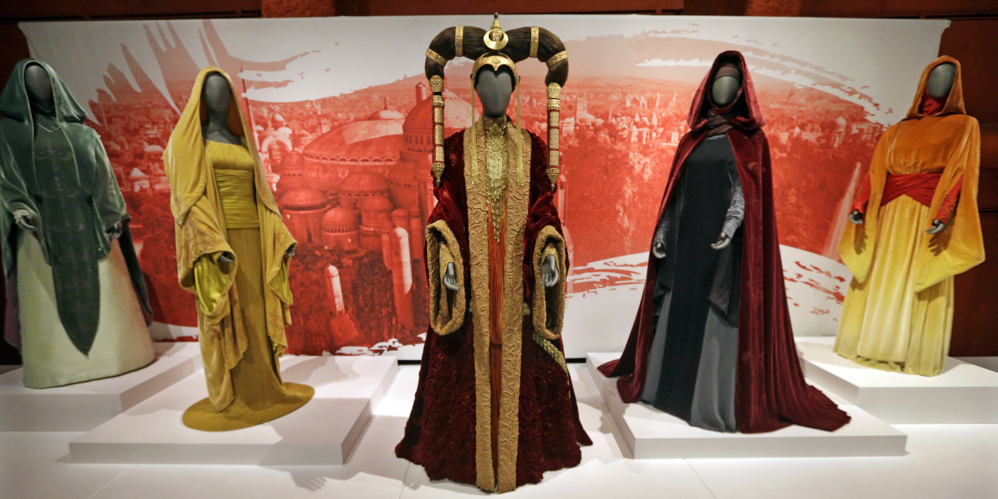 "In this photo taken Thursday, Jan. 29, 2015, the Senate gown of Queen Amidala, center, is seen with handmaiden gowns on display as part of an exhibit on the costumes of Star Wars at Seattle's EMP Museum. The creators of the new exhibit, with 60 original costumes from the six Star Wars movies, are hoping to gather geeks, fashionistas and movie fans together to discuss how clothing helps set the scene. The exhibit, ""Rebel, Jedi, Princess, Queen: Star Wars and the Power of Costume,"" will be in Seattle through early October and then travel across the United States through 2020. (AP Photo/Elaine Thompson)"