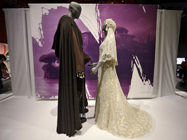 "In this photo taken Thursday, Jan. 29, 2015, Anakin Skywalker's Jedi robe and the wedding gown of his bride, Padme Amidala, are displayed as part of an exhibit on the costumes of Star Wars at Seattle's EMP Museum. The creators of the new exhibit, with 60 original costumes from the six Star Wars movies, are hoping to gather geeks, fashionistas and movie fans together to discuss how clothing helps set the scene. The exhibit, ""Rebel, Jedi, Princess, Queen: Star Wars and the Power of Costume,"" will be in Seattle through early October and then travel across the United States through 2020. (AP Photo/Elaine Thompson)"