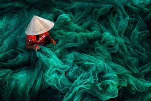 PHAN RANG FISHING NET MAKING  Author: Danny Yen Sin Wong (MY)  Location: Vietnam  Description: In a small village in southern Vietnam near Phan Rang, a woman wearing a typical cone hat is creating a fishing net in their traditional manner. The manufacturing of handmade nets is still a typical Vietnamese activity for women which they carry on while their husbands are out fishing.